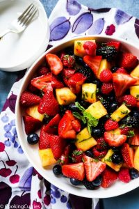 Mixed berries and pineapple in a bowl with a mint dressing on top