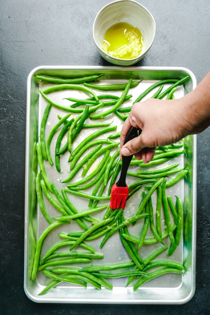 Brushing garlic oil with a silicone basting brush on the green beans spread out on a sheet pan