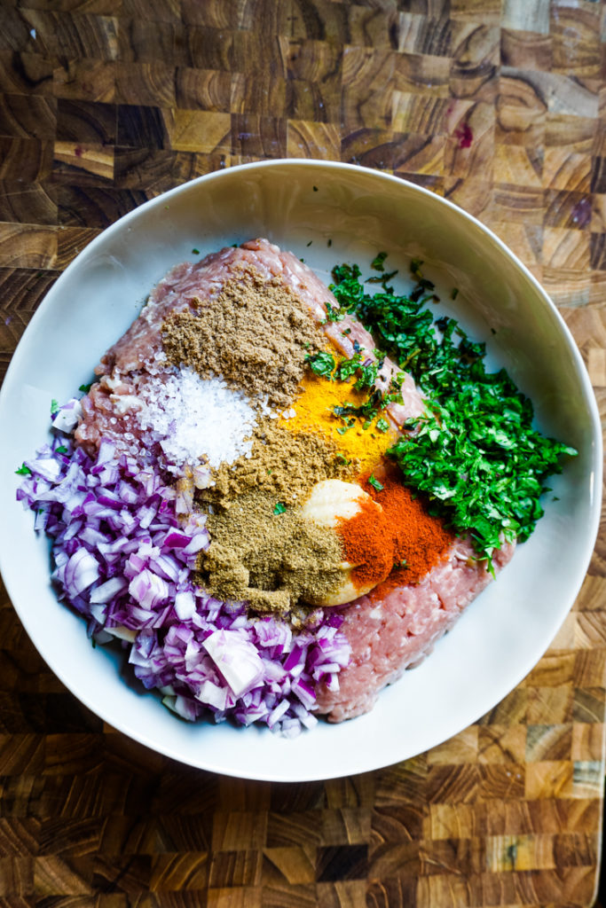 Ground turkey in a white bowl with onions, herbs and spices on top of it