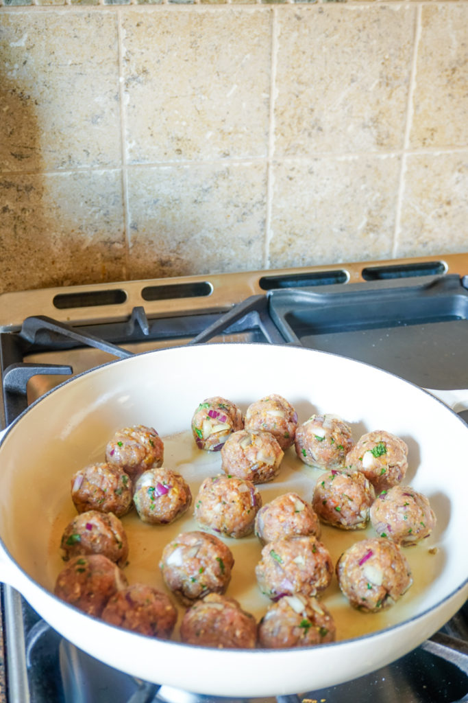 Meatballs cooking in a white cast iron pan on the stove