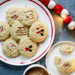 Cookies on a white plate with red rimwith a cup of coffee on the side of the plate