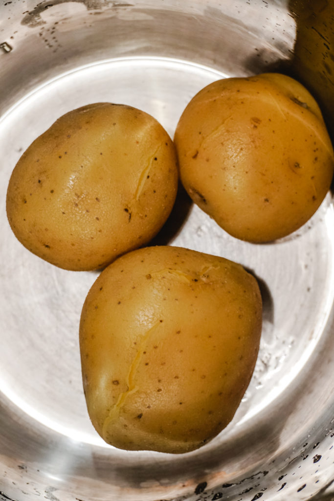 In process shot of boiled potatoes in their skin