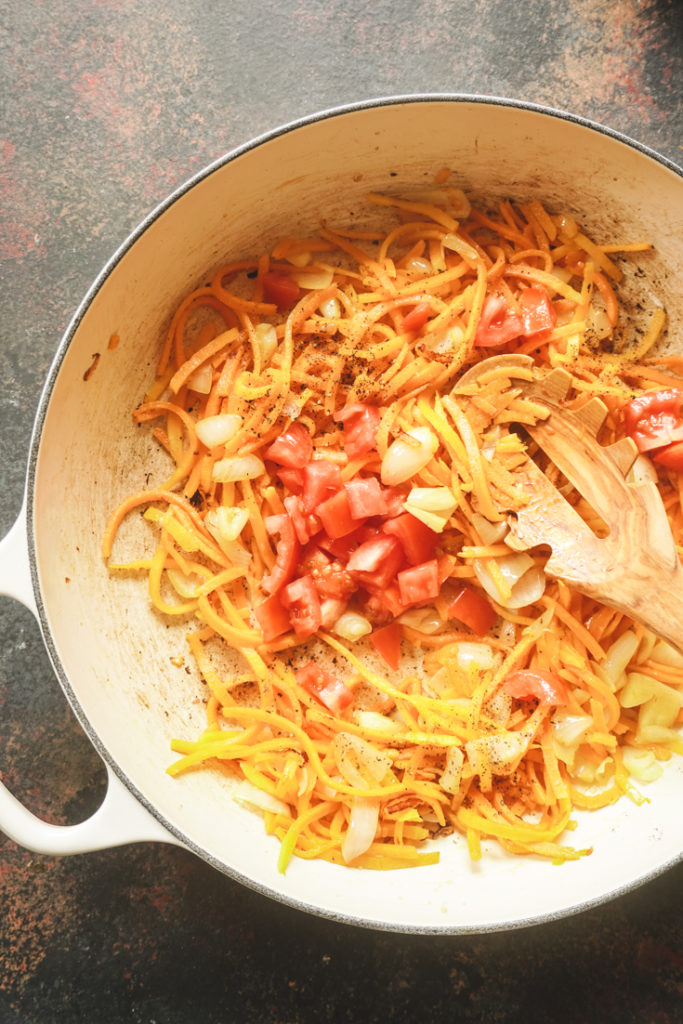 Top shot of process of making butternut noodles in a white cast iron pan, step of adding tomatoes to it