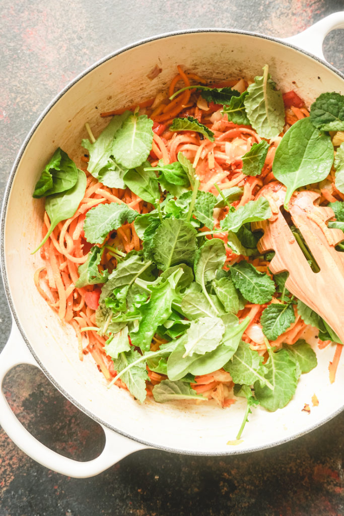 Top shot of process of making butternut noodles in a white cast iron pan, step of adding arugula to it