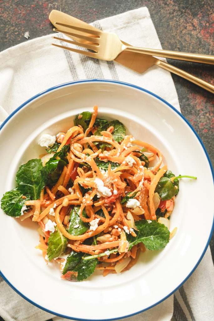Butternut noodles in a white bowl with gold fork and knife on the side