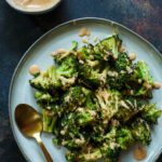 Top shot of Roasted Broccoli on a grey plate and drizzled with tandoori ranch on top, gold spoon on side of the plate