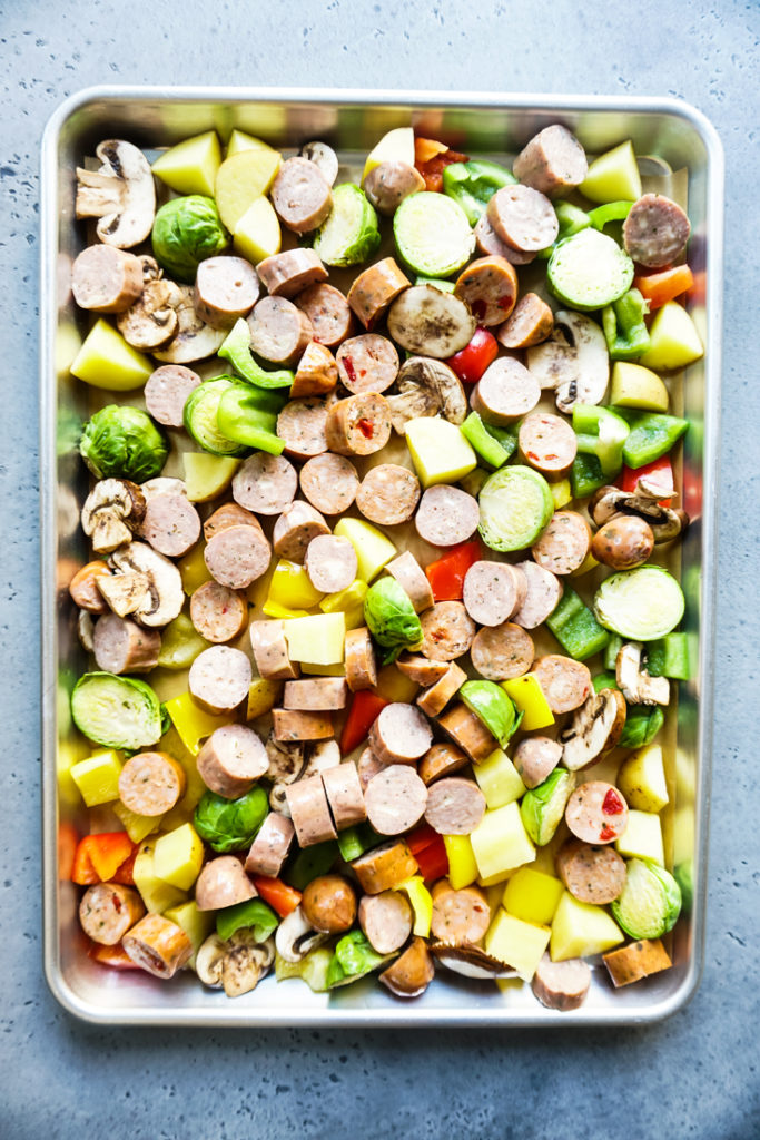 sausage and veggies lined up in a sheet pan