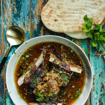 Short ribs curry in a bowl with two naans on the side