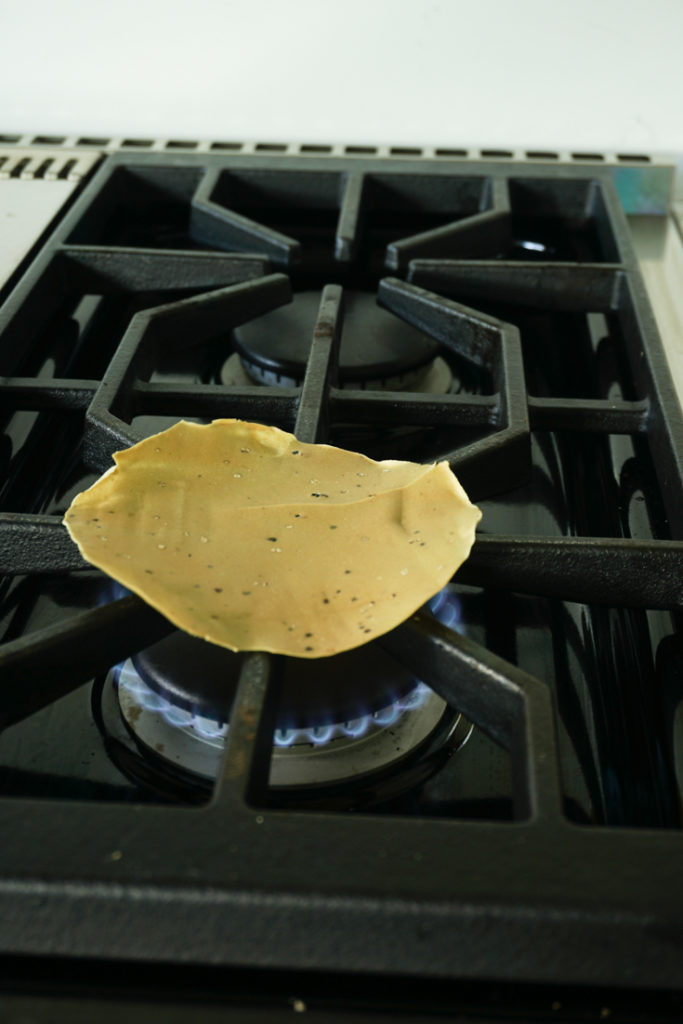 Papad being roasted on open flame of a gas stove