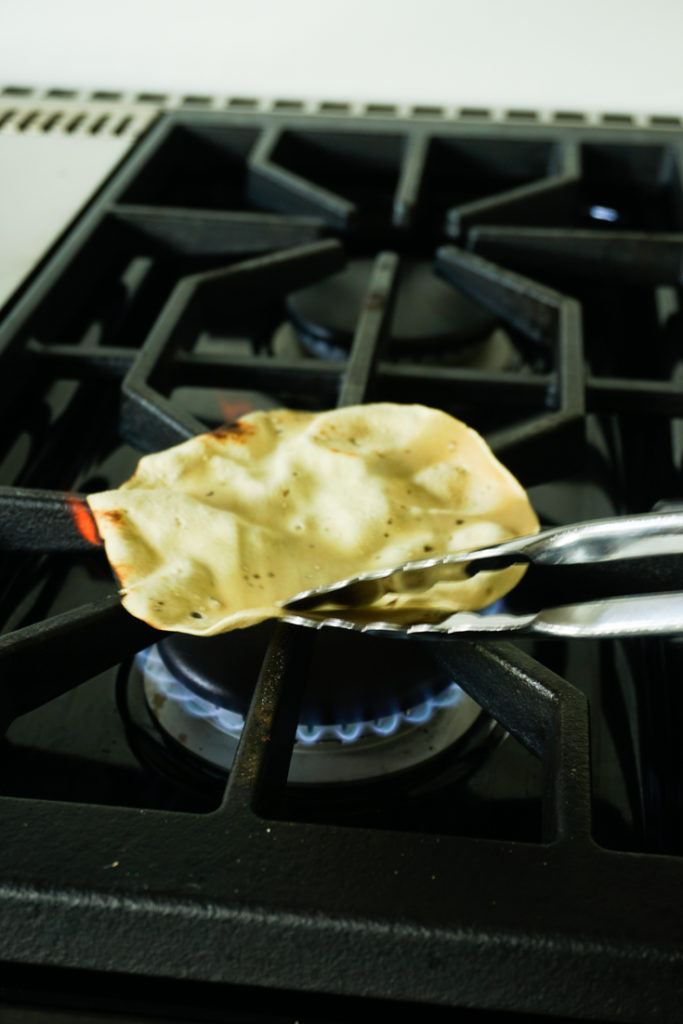 Papad held with a pair of tongs roasting on an open flame of a gas stove