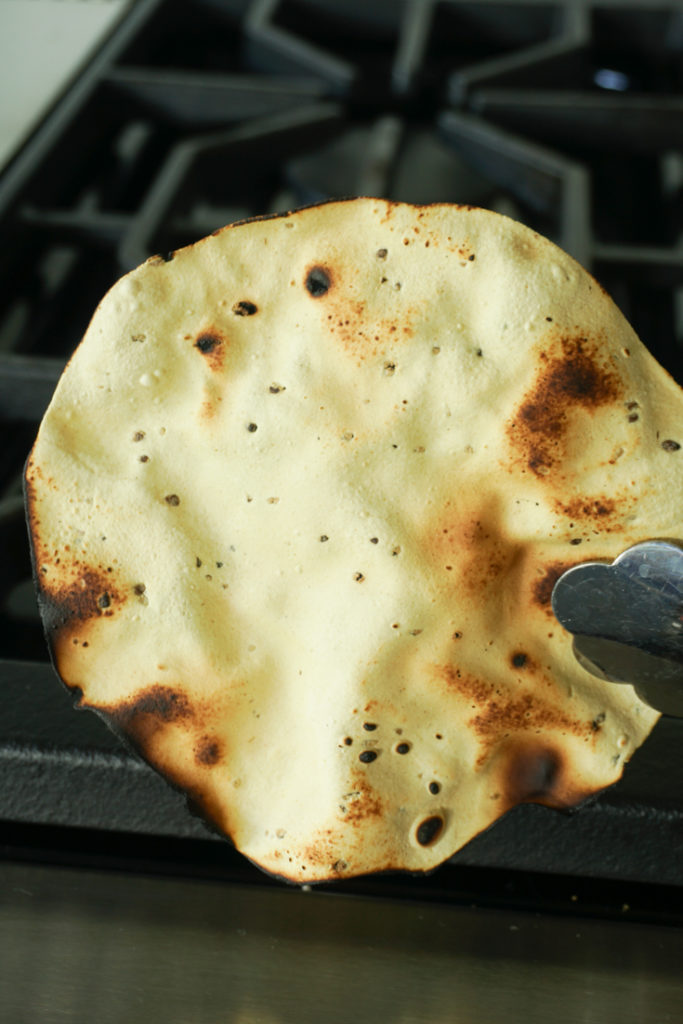 Roasted papad held with a pair of tongs to show what it should look like
