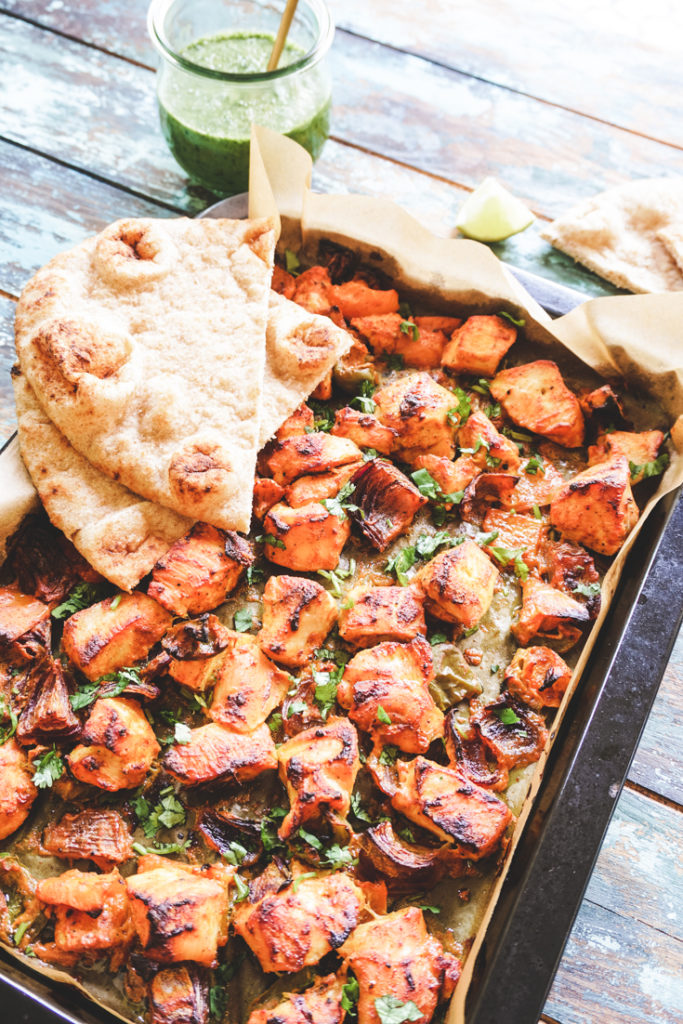 Angle shot of sheet pan with chicken tikka and two naans placed on top of it