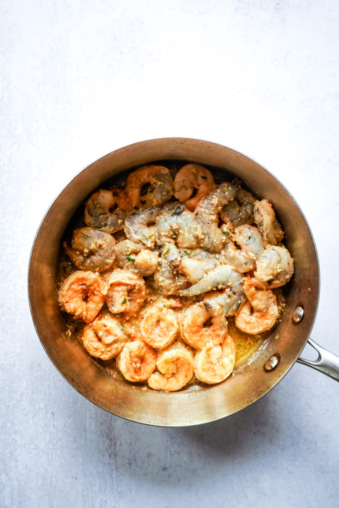 Part of the shrimp in the pan flipped over after cooking to show how it should look