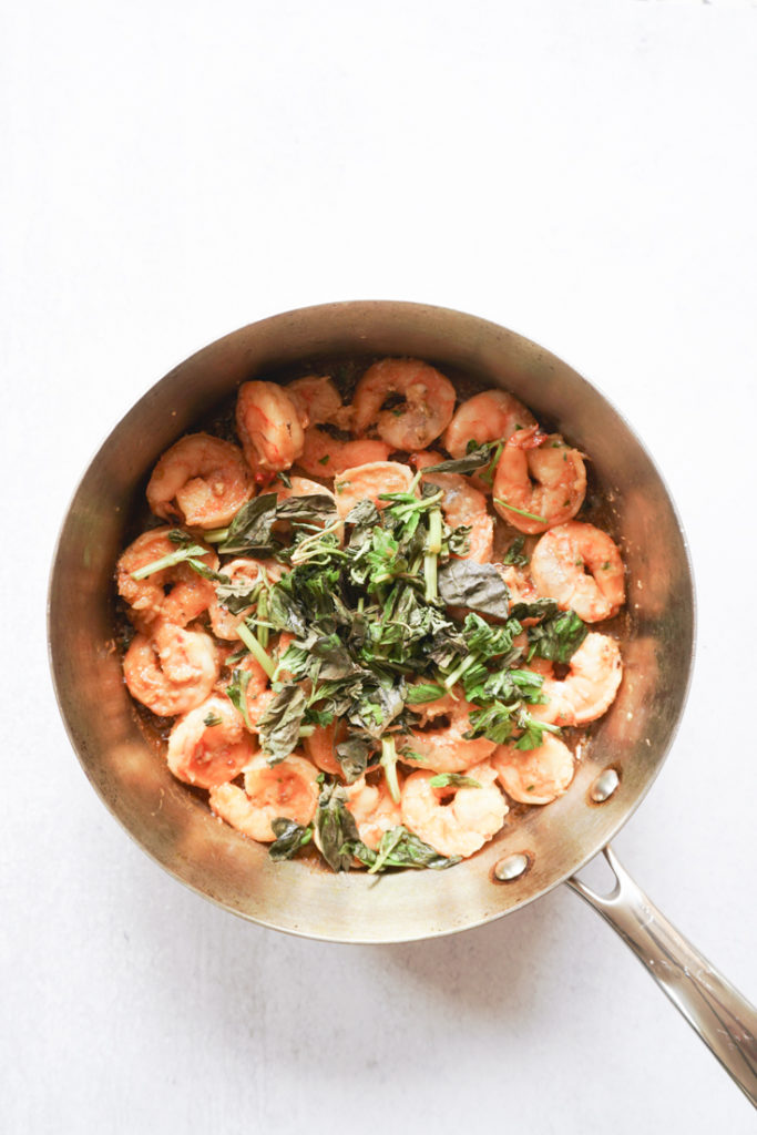 Basil on top of shrimp in a saute pan