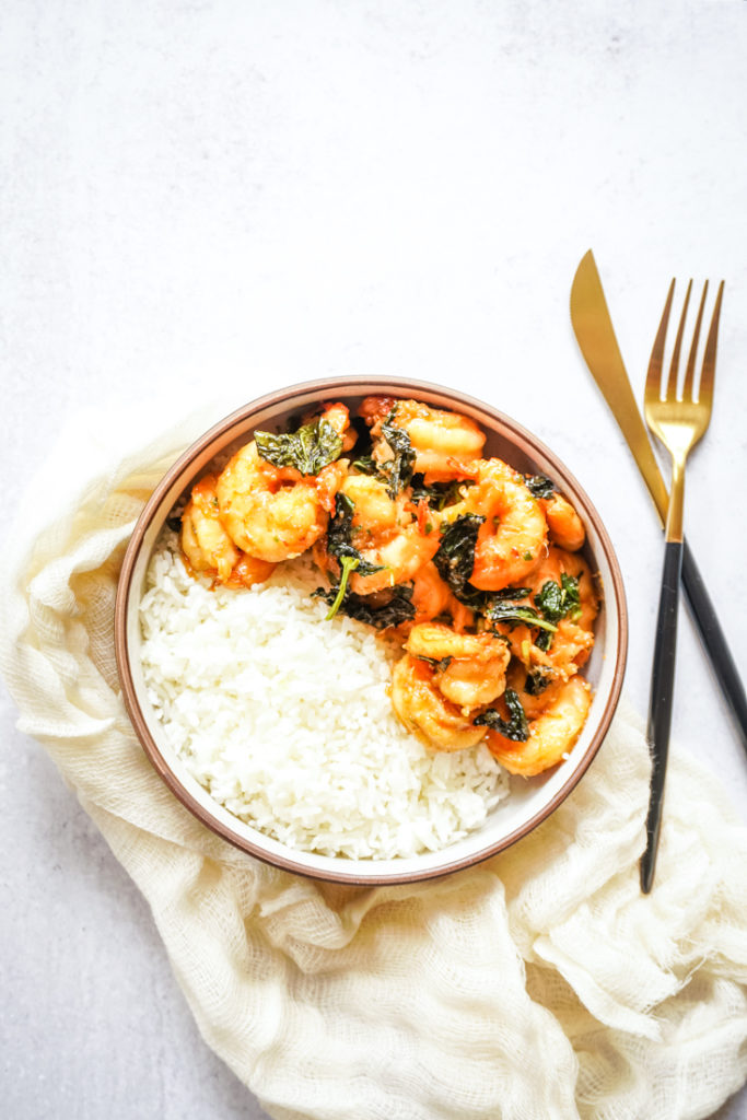 Top shot of shrimp and basil with rice in a bowl with black and gold flatware on the side