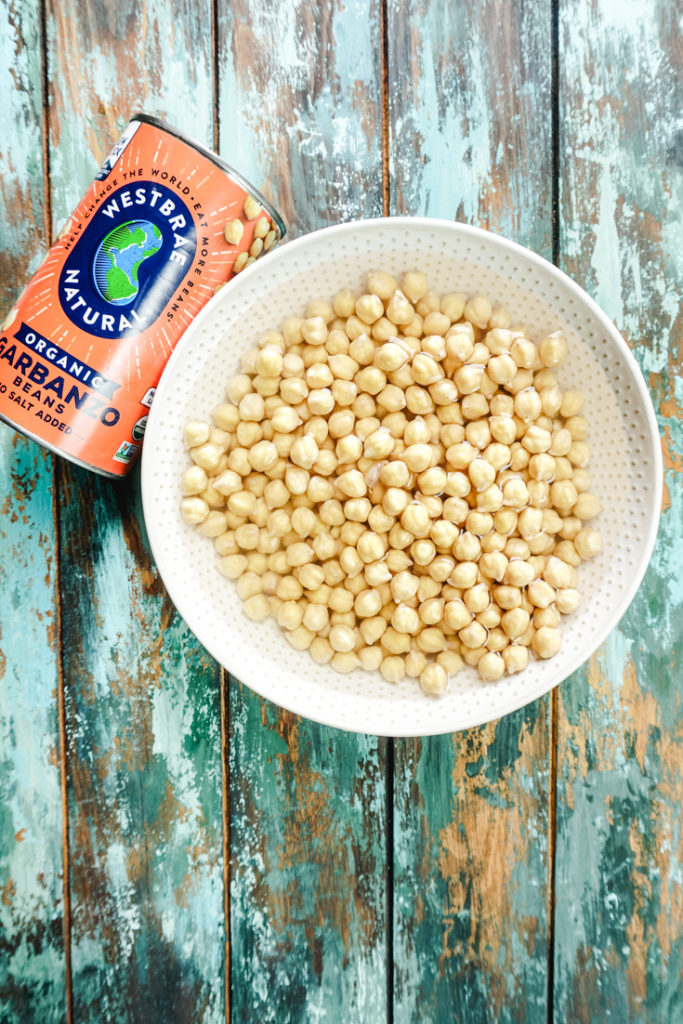 cooked chickpeas in a bowl with a can of chickpeas on the side