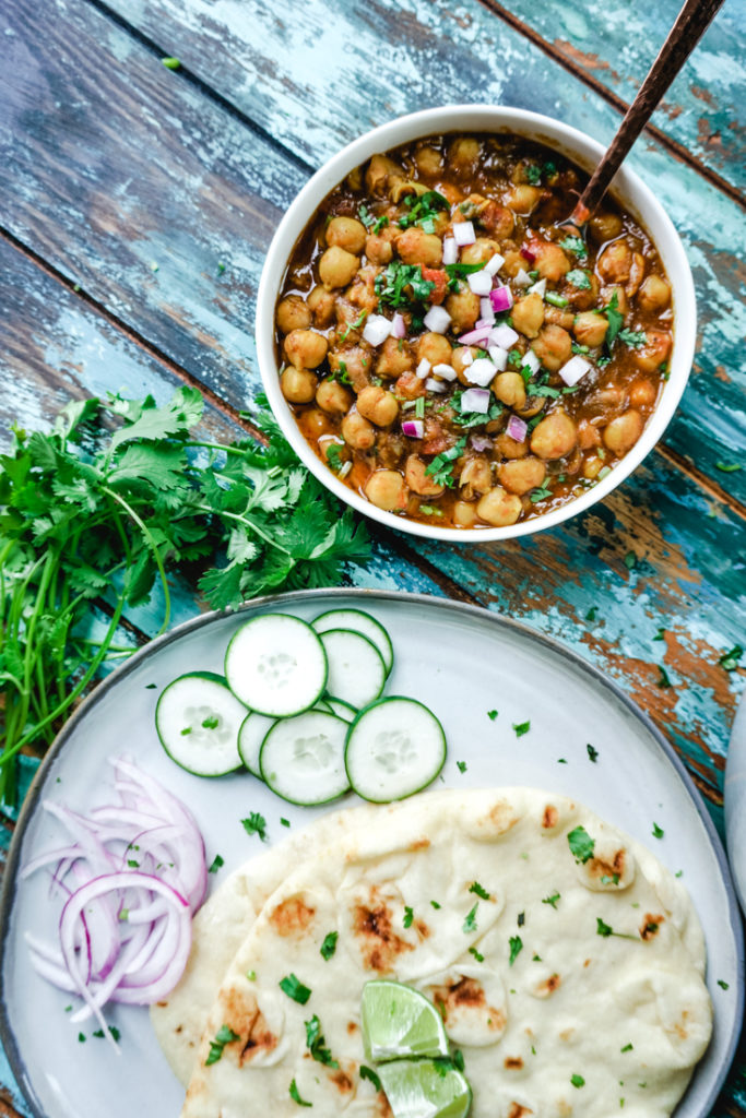 Chana Masala in a white bowl with some naan on a plate next to it