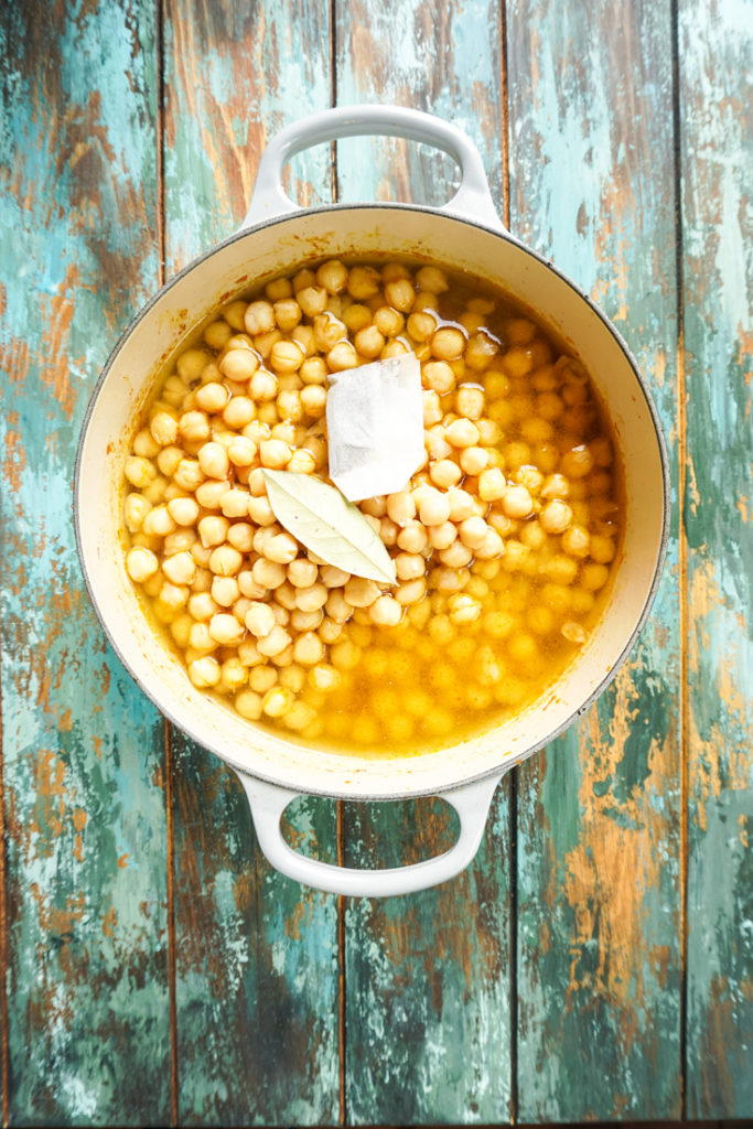 Cooked chickpeas in water topped with a bay leaf and a tea bag