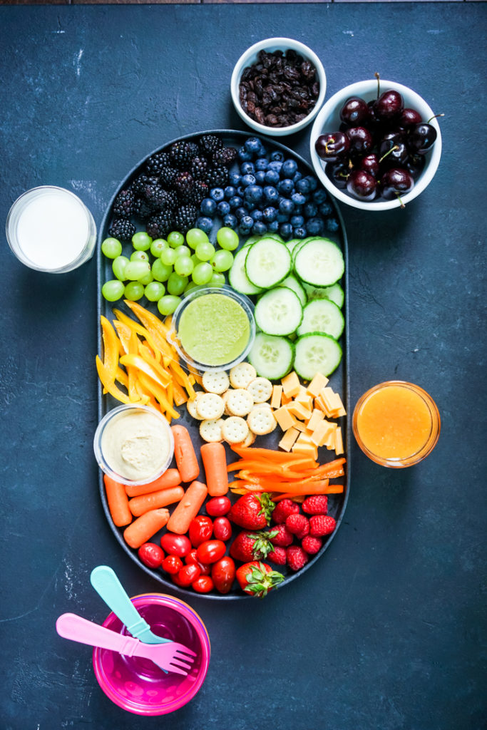 Top shot of a platter with rainbow colored snacks with a glass of milk and a glass or orange juice next to it