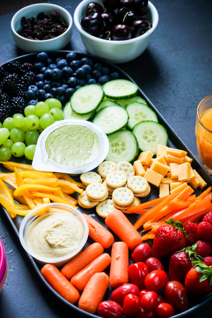 Angle shot of a snack board with rainbow colored snacks in it
