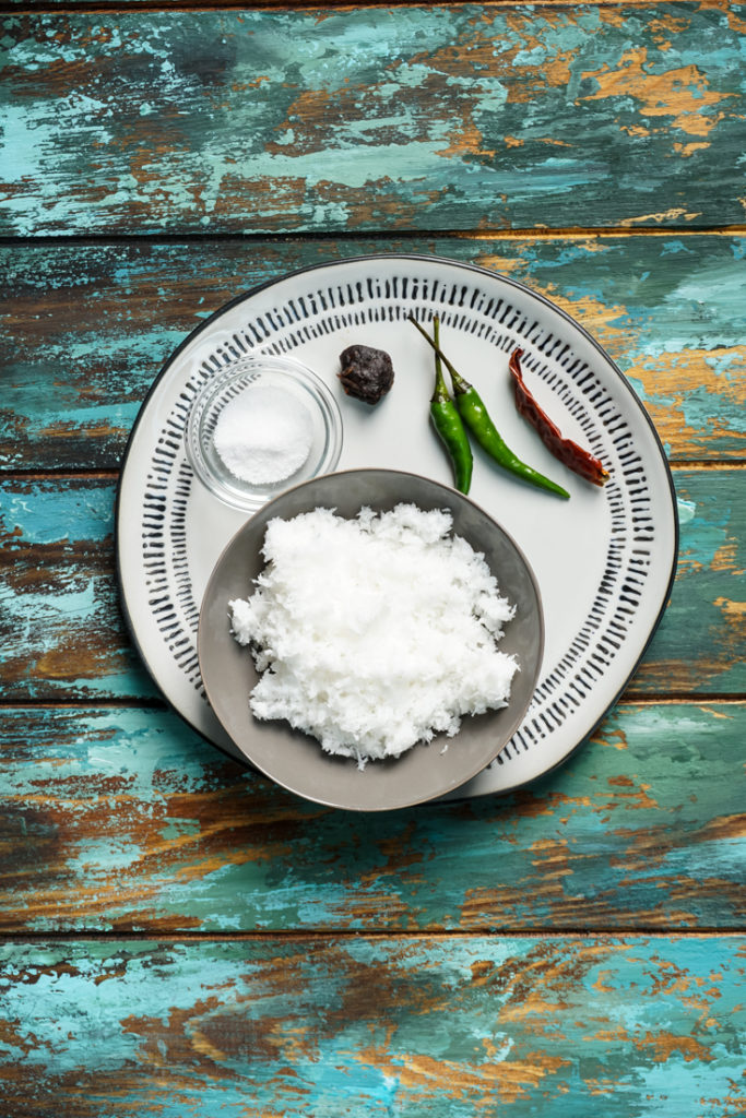 Ingredients for coconut chutney - grated coconut, green chillies, red chillie, tamarind and salt in a plate
