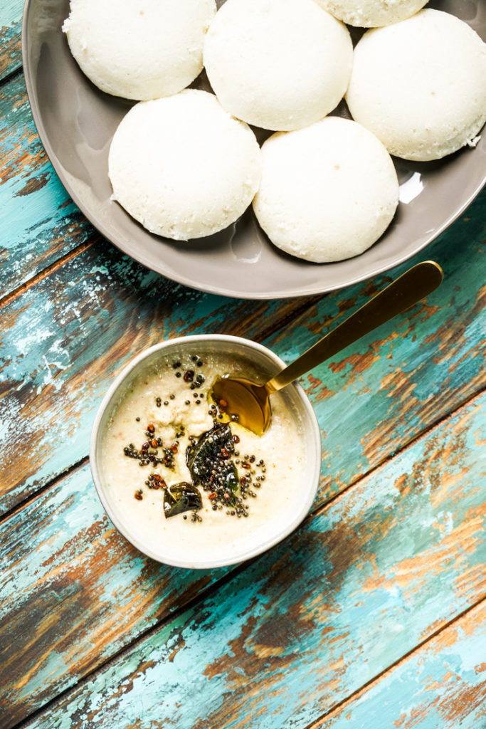 Coconut Chutney in a bowl with a gold spoon in it and a plate of idlis on the side