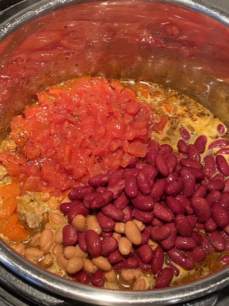 Kidney beans, pinto beans and canned tomatoes on top of the rest of the ingredients for turkey chili in the instant pot