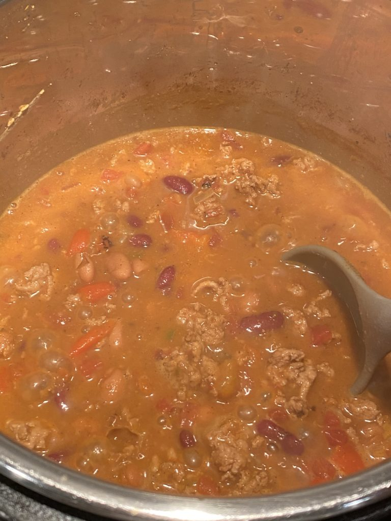 Turkey chili in the instant pot with a ladle in it