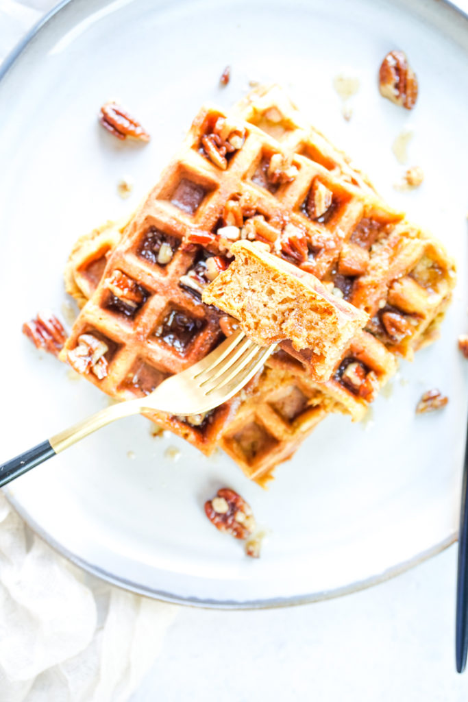 Fork in a piece of waffle on top of two waffles stacked on top of each other