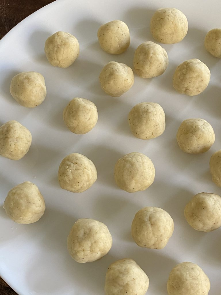 gulab jamun dough balls placed on a white plate