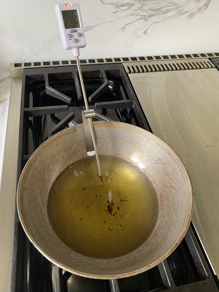 a kadhai on stove with oil in it and a candy thermometer plugged in