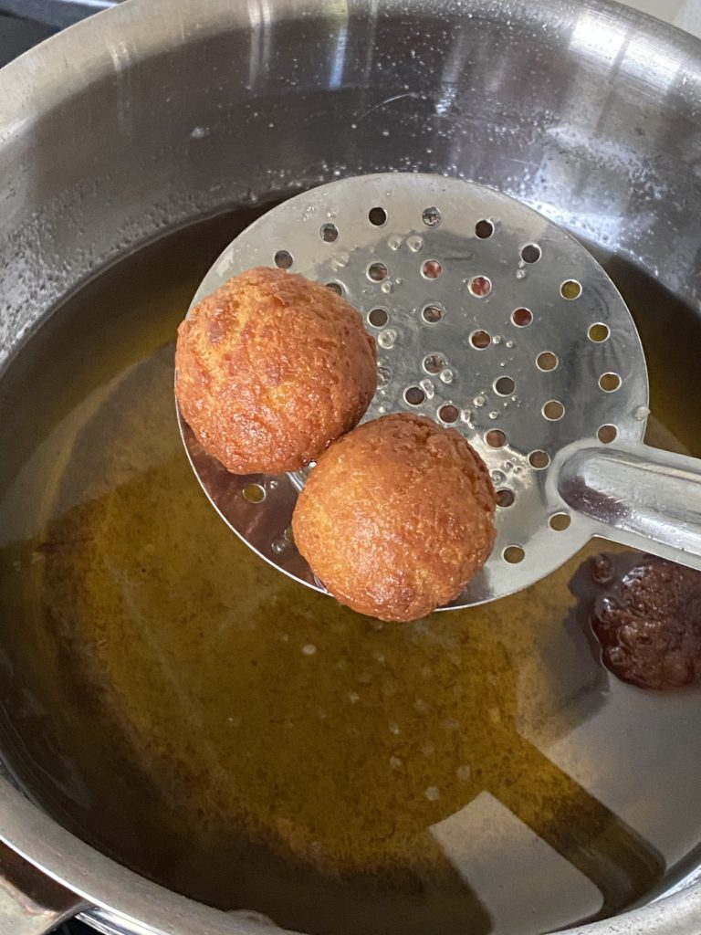 ladle adding the fried gulab jamun balls in sugar syrup