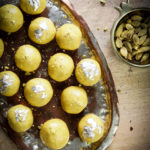 Besan laddoos in a silver platter placed on a wooden board