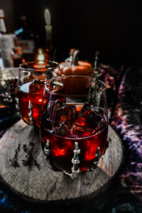 Spooky red cocktail in a skeleton hand stemless wine glass