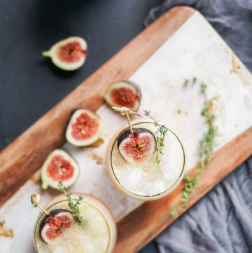 Two glasses with cocktails on a paddle board with figs around it