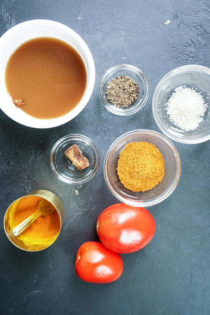 spices and two tomatoes laid out to make rasam rice