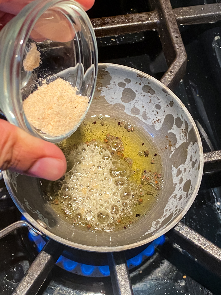 small pan with oil in it and a hand adding spices to it