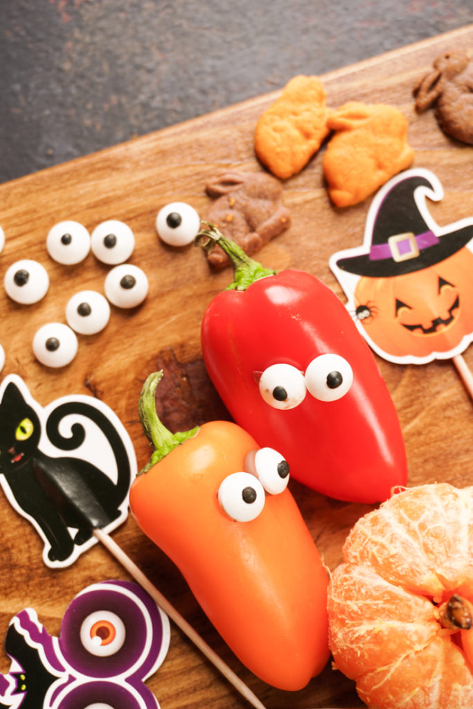orange and red bell pepper with candy eyes stuck on them