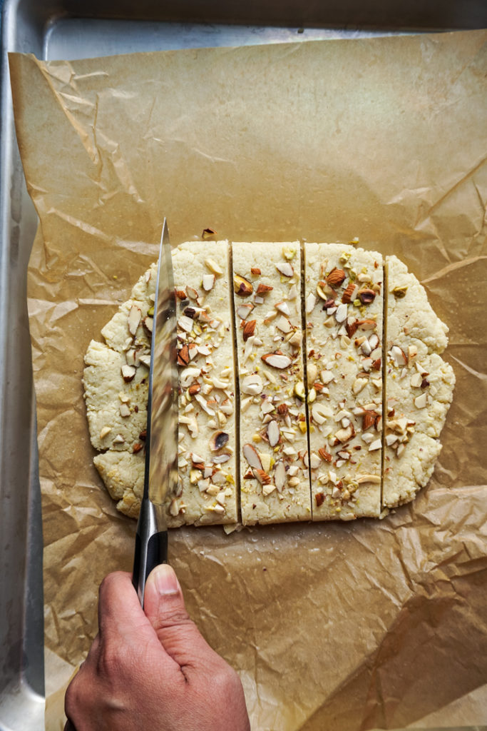 Knife cutting the burfi into squares