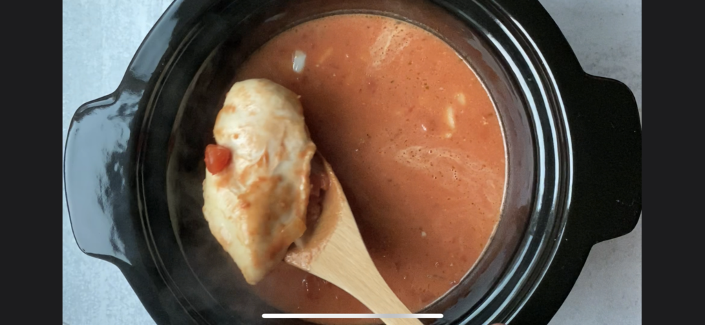 Wooden ladle scooping out a chicken breast from the crockpot