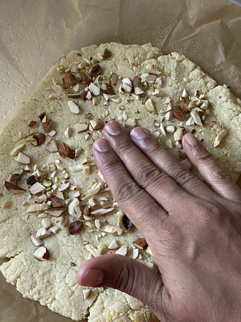 hand pressing down chopped mixed nuts onto the burfi