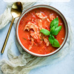 a bowl of tomato chicken soup with basil leaves garnish and text on the image
