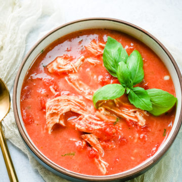 Bowl of tomato chicken soup with basil for garnish