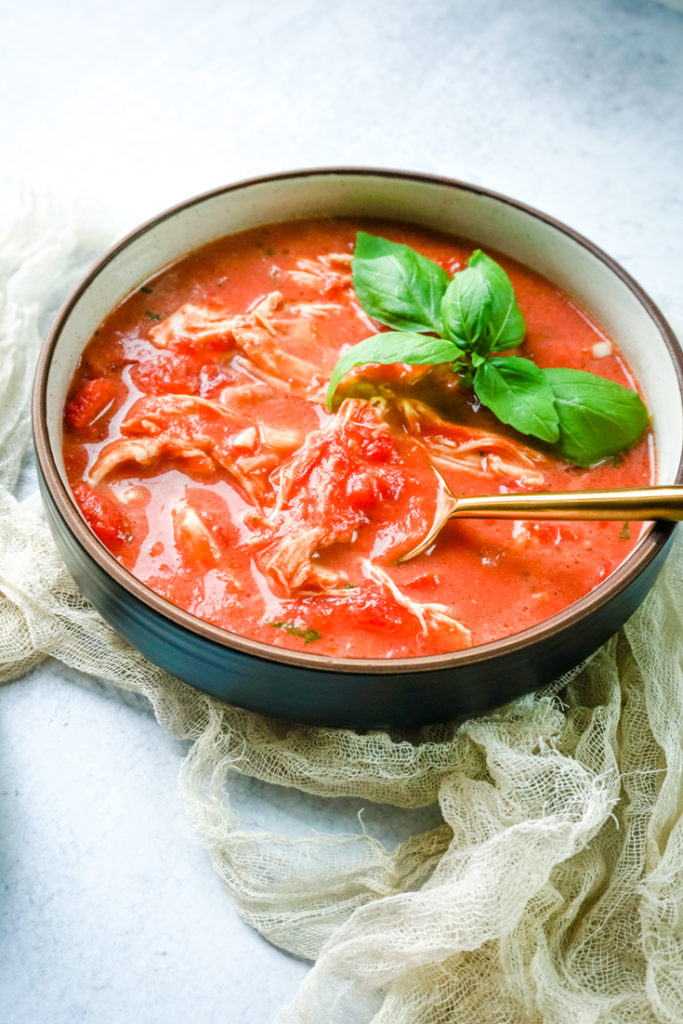 Bowl of tomato chicken soup with a gold spoon in it