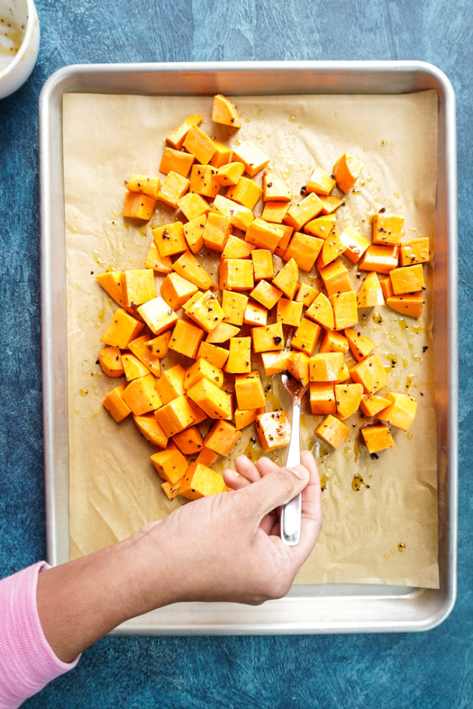 hand mixing sweet potatoes in a baking tray
