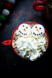 Hot chocolate topped with snowman marshmallows and whipped cream
