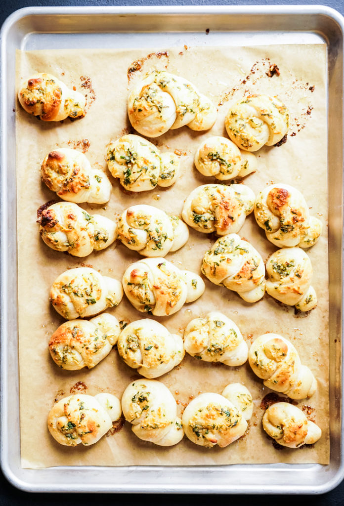 Garlic knots lined up in a baking sheet