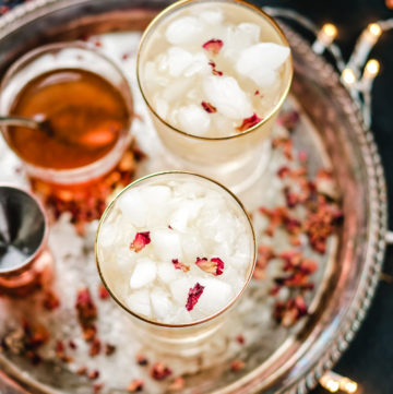 cardamom rose cocktail in two gold rimmed glasses on a silver platter
