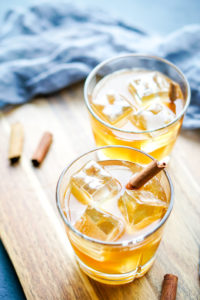 two glasses of maple whiskey sour on a wood board