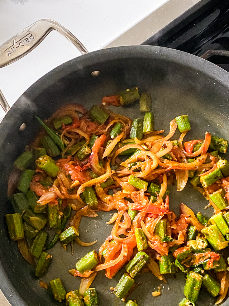 okra with sauteed onions and tomatoes in a saute pan